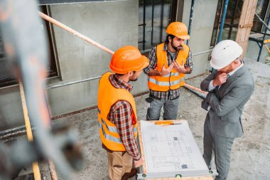 High angle view of confused builders and architect discussing building plan at construction site stock vector