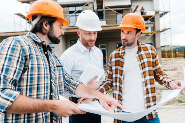 Group of architects with building plan having conversation in front of construction site stock vector