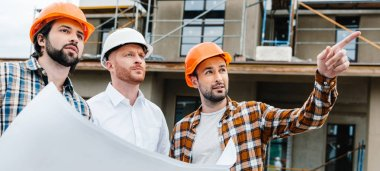 wide shot of group of architects with building plan standing in front of construction site and looking away