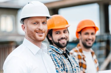 Group of smiling architects in hard hats looking at camera stock vector