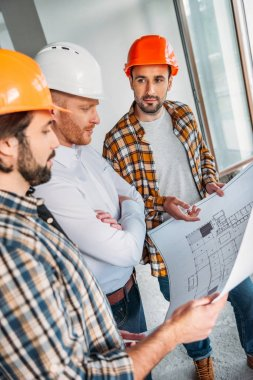 group of architects with blueprint having conversation inside of constructing building