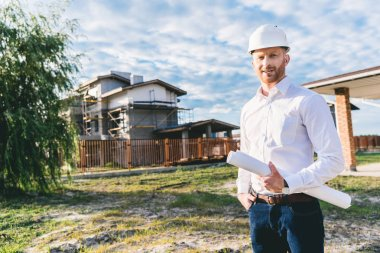 handsome architect in white shirt with blueprint standing at yard in front of building house