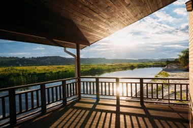 view of beautiful sunset over river from wooden terrace