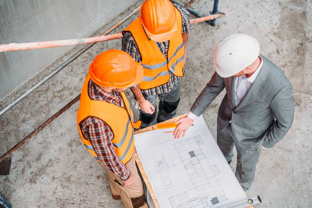 High angle view of builders and architect discussing blueprint at construction site stock vector