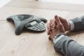 Oříznout záběr podnikatel v obleku sedí v přední části konference telefon na stole v kanceláři