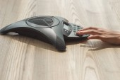 Fotografie cropped shot of businesswoman pushing button of speakerphone on wooden table