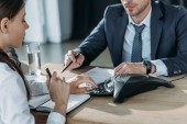 oříznutý snímek podnikatel a podnikatelka pomocí konference v moderní kanceláři