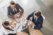 pohled z vysokého úhlu podnikatelů během konverzace v moderní kanceláři pomocí sluchátek s mikrofonem
