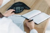 Fotografie cropped shot of businesswoman with contract pushing button of conference phone on table at office