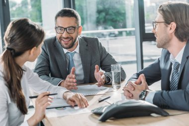 confident business people having conversation and using speakerphone at modern office