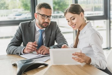 businessman and beautiful young businesswoman using tablet together at modern office
