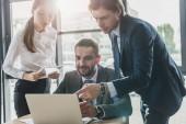 Erfolgreiche Geschäftsleute nutzen gemeinsam Laptop im modernen Büro