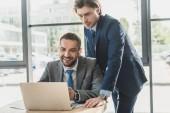 gut aussehende erfolgreiche Geschäftsleute, die gemeinsam mit Laptop im modernen Büro arbeiten