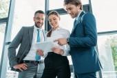 Blick von unten auf zufriedene Geschäftsleute, die gemeinsam Tablet im modernen Büro nutzen