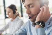 Photo handsome call center manager in headphones with mike sitting at workplace while his colleague sitting on background