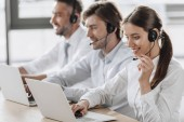 Fotografie smiling call center managers in white shirts working together while sitting in row at modern office