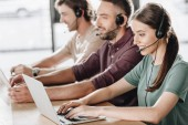 Photo happy team of call center managers working together while sitting in row at modern office