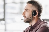 Fotografie side view of handsome call center worker in headphones with microphone
