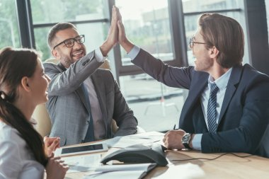 happy business people giving high five during meeting at modern office