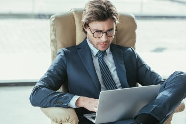 handsome focused businessman sitting in armchair and using laptop