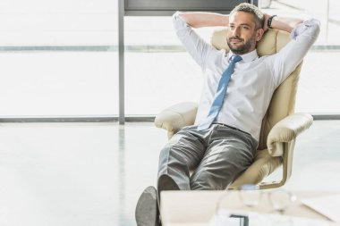 handsome businessman relaxing on luxury armchair at modern office
