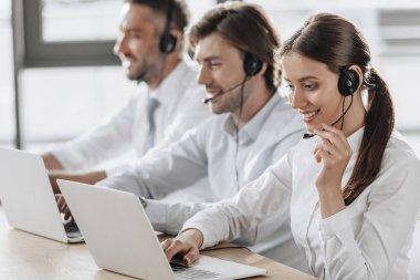 çağrı merkezi yöneticileri birlikte satırda modern ofiste otururken çalışan beyaz gömlek gülümseyen