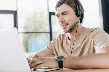 smiling young support hotline worker with laptop and headphones at workplace