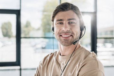 close-up portrait of smiling young support hotline worker with headphones