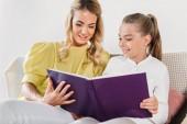 Fotografie matka a dcera sedí na gauči a čtení knihy doma