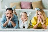šťastné mladé rodiny leží na podlaze doma a při pohledu na fotoaparát