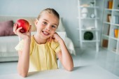 Fotografie adorable little child with red apple sitting at home
