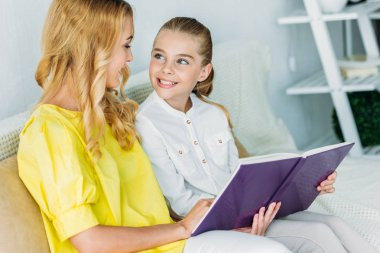 smiling mother and daughter sitting on couch and reading book at home