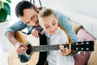 happy father and daughter playing guitar together at home