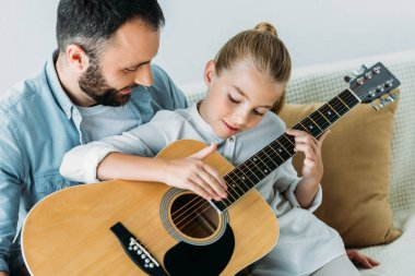 Father and daughter playing guitar together at home stock vector