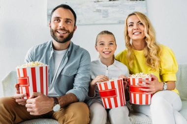 smiling young family watching movie at home with buckets of popcorn
