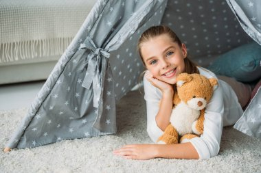 adorable little child lying on floor in teepee with teddy bear at home