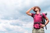 turistica attraente in cappello che osserva via, con sfondo di cielo nuvoloso
