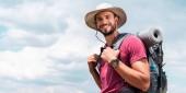 usměvavé cestující v klobouku s batohem a turistické mat, zamračená obloha pozadí