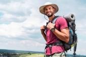 usměvavé cestující v klobouku s batohem a turistické mat při pohledu na fotoaparát