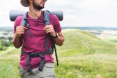 Photo cropped view of traveler with backpack and tourist mat walking on meadow