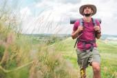 Fotografie hezký turista v klobouku s batohem a turistické mat chůzi na cestě na zelené louce