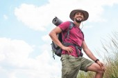 smiling hiker in hat with backpack and tourist mat