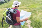 Fotografie male hiker in hat with backpack, thermos, tourist mat and map