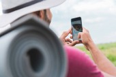 Fotografie hiker with backpack and tourist mat taking selfie on smartphone