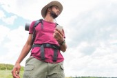 Photo bottom view of handsome traveler with backpack using smartphone