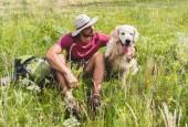Reisenden in Hut sitzend mit golden Retriever Hund auf grüner Wiese