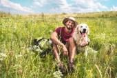 viaggiatore maschio che si siede con il cane sul prato verde di estate