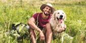 Reisende, die mit golden Retriever Hund auf grüner Wiese sitzen