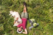 Blick von oben auf Touristen und Golden Retriever Hund liegt auf grünem Gras mit Rucksack
