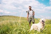 Photo traveler with backpack walking with golden retriever on summer meadow with cloudy sky